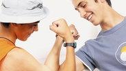 Jugendliche beim Armdrücken auf dem Autodach eines Käfers. © plainpicture/Oliver Rüther Fotograf: Oliver Rüther