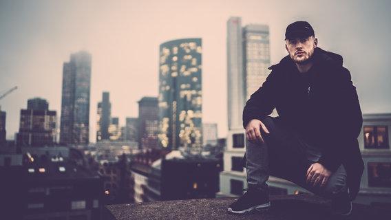 Rapper Bausa auf einem Hausdach.