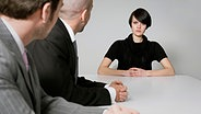 Junge Frau sitzt mit ernstem Blick zwei Männern im Büro gegenüber © picture-alliance / beyond/diffus Fotograf: beyond/diffused