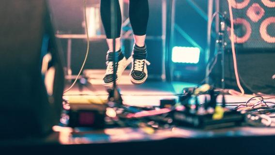 Eine Musikerin oder ein Musiker springt auf einer Bühne in die Luft. © hoffi99 / photocase.de Foto: hoffi99 / photocase.de