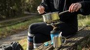 Jemand kocht draußen auf einem Campingkocher. © picture alliance / dpa-tmn | Christin Klose Foto: Christin Klose