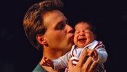 Ein Vater hält Baby zärtlich im Arm und küsst es. © picture-alliance / Helga Lade Fotoagentur GmbH, Ger Fotograf: K.Schmied