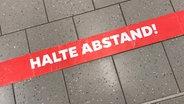 """Auf dem Boden klebt ein Streifen mit der Aufschrift """" Halte Abstand"""" © imago-images Foto: Waldmüller"""