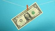 Eine 1-Dollar-Note hängt mit einer Wäscheklammer auf einer Wäscheleine.