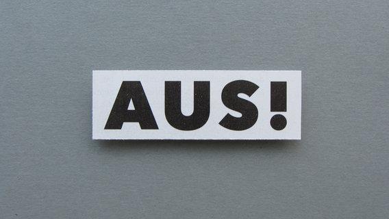 """Zu sehen ist das Wort """"AUS"""" auf einem grauen Hintergrund. © knallgrün / photocase.de Foto: knallgrün"""