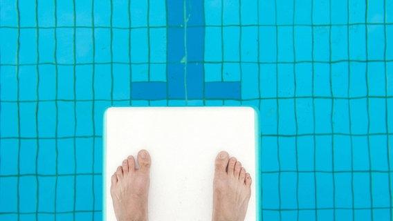 Zwei Füße stehen auf einem Sprungbrett - darunter ist Wasser zu sehen. © imago/blickwinkel