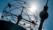 Die Sonne strahlt am Alexanderplatz in Berlin hinter der Weltzeituhr und dem Fernsehturm. ©  picture alliance / dpa Foto: Hauke-Christian Dittrich