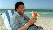 Einen tropischen Drink genießt Roberto Blanco am 16.5.2002 am Strand von Varadero. © dpa - Fotoreport Foto: Wolfgang Langenstrassen
