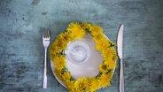 Zu sehen ist ein Teller aus der Vogelperspektive, auf dem ein Löwenzahn-Kranz liegt. © imago / Westend61
