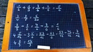 Zu sehen ist eine Schultafel, auf die mit Kreide verschiedene Rechnungen und Aufgaben geschrieben wurden. © picture alliance/chromorange Foto: CHROMORANGE / Martina Rädlein