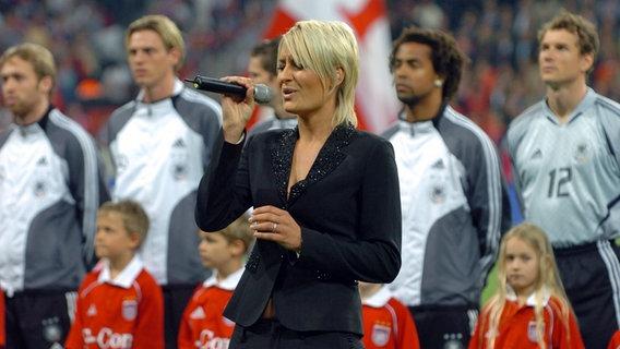 Sarah Connor versucht 2005 in der Allianz-Arena in München, die deutsche Nationalhymne zu singen. © picture-alliance / Sven Simon