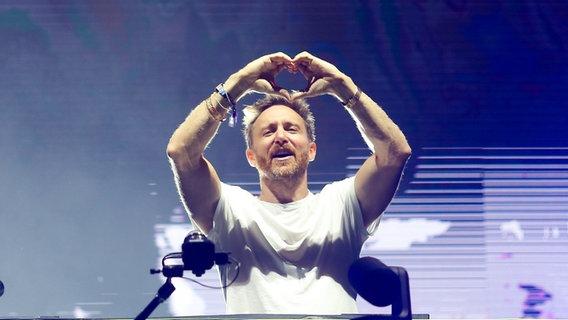 David Guetta steht am DJ-Pult und formt mit seinen Händen ein Herz. © picture alliance/PIXSELL Foto: Borna Filic