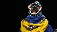 Ein übertrieben verkleidetes Model mit Maske auf einem Laufsteg © dpa - Report