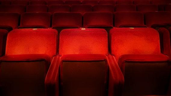 Rote Kinosessel in einem Saal. © rarrarorro / photocase.de Foto: rarrarorro / photocase.de
