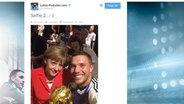 Twitter-Screenshot: Selfie von Lukas Podolski mit Angela Merkel und dem WM-Pokal © Twitter.com