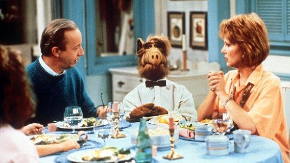 Der Außerirdische Alf (M) mit seinen Gasteltern Tanner, dargestellt von Max Wright und Ann Schedeen. © dpa - Bildarchiv