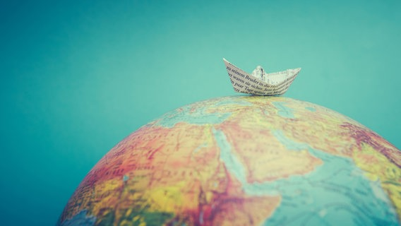 Ein Papierschiffchen liegt auf einem Globus. © suze / photocase.de Foto: suze