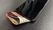 Geldscheine stecken in einer Handyhülle. © NDR/N-JOY