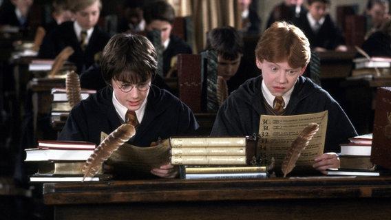 """Eine Filmszene aus """"Harry Potter und die Kammer des Schreckens"""": Harry und Ron sitzen im Klassenzimmer in Hogwarts. © picture alliance/United Archives Foto: United Archives/Impress"""