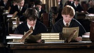 "Eine Filmszene aus ""Harry Potter und die Kammer des Schreckens"": Harry und Ron sitzen im Klassenzimmer in Hogwarts. © picture alliance/United Archives Fotograf: United Archives/Impress"