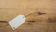 Ein Geschenk-Anhänger auf Holzgrund © David Dieschburg / photocase.de Fotograf: David Dieschburg