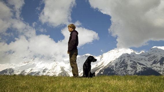 Herrchen und Hund stehen Rücken an Rücken in einer Berglandschaft. © Christian Redolfi / photocase.de Foto: Christian Redolfi