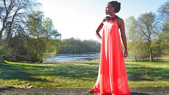 Die Sängerin Ivy Quainoo in einem roten Kleid an einem See. © Universal Foto: Michael Zargarinejad