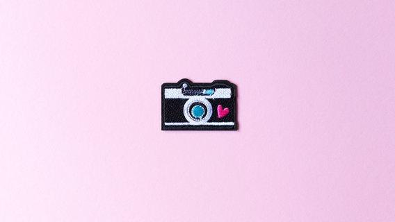 Ein Nähsticker in Form einer Kamera auf rosa Hintergrund. © go2 / photocase.de Foto: go2 / photocase.de