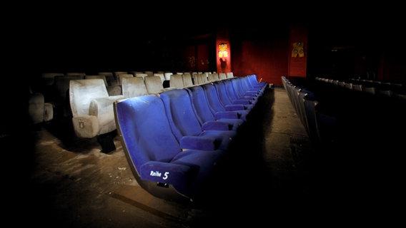 Ein schwach beleuchteter alter Kinosaal mit alten Kinosesseln. © kallejipp / photocase.de Foto: kallejipp