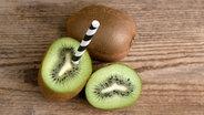 Aufgeschnittene Kiwi, in der ein Strohhalm steckt. © kb-photodesign / photocase.de Foto: kb-photodesign