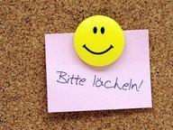 """Zu sehen ist ein PostIt auf einer Pinnwand, auf dem steht """"Bitte lächeln!"""" und darüber ein Smiley. © picture alliance/chromorange Fotograf: Christian Ohde / CHROMORANGE"""