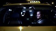 Taxifahrer sitzt nachts im Taxi © Timo Großpietsch