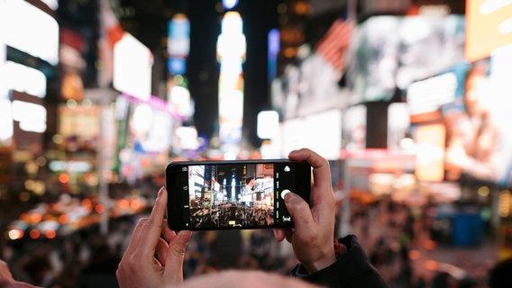 Ein Mann fotografiert den Times Square in New York. © picture alliance / ZB Foto: Gregor Fischer