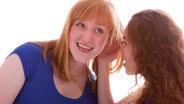 Eine Frau flüstert einer anderen etwas zu. © picture alliance/chromorange Foto: Lorenz Timm / CHROMORANGE