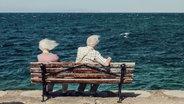 Zu sehen ist ein altes Paar, das auf einer Bank am Meer sitzt und vom Wind durchgepustet wird. © joexx / photocase.de Fotograf: joexx