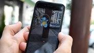 """Auf einem Smartphone wird in """"Pokémon Go"""" Glumanda gefangen. © picture alliance / dpa Themendienst Fotograf: Andrea Warnecke"""