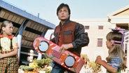 """Zu sehen ist eine Szene aus dem Film """"Zurück in die Zukunft 2"""", in der Marty McFly auf einem schwebenden Auto steht. © imago"""