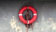 Ein Rettungsring hängt an der Wand. © Flügelfrei / photocase.de Fotograf: Flügelfrei