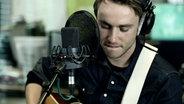 Clueso mit Gitarre am Mikrofon im N-JOY Studio. © N-JOY / NDR