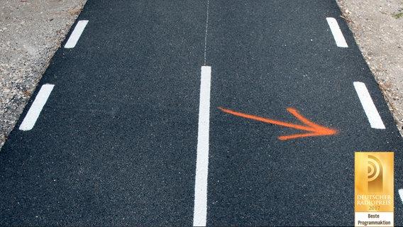 Ein Pfeil auf einer Straße © raperonzolo / photocase.de Foto: raperonzolo
