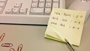 Auf einem Post-it stehen in Büro-Atmosphäre Fußballergebnisse geschrieben. © NDR/ Pascal Strehler Foto: Pascal Strehler