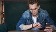 Ein junger Mann schaut auf seine Armbanduhr © imago/Westend61