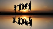 Fünf Jugendliche springen am Strand dem Sonnenuntergang entgegen. © Photocase Fotograf: Emanoo