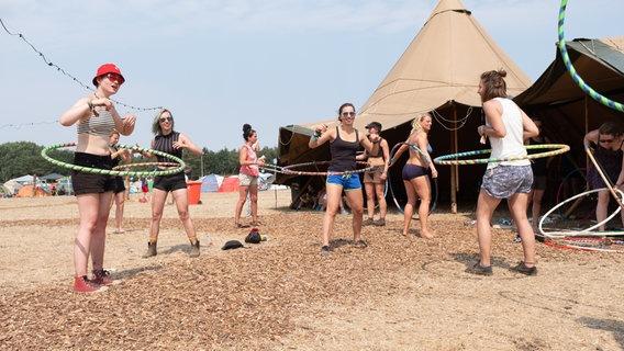 Mehrere Frauen üben mit Hula Hoop Reifen. © NDR Foto: Benjamin Hüllenkremer