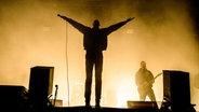 Der Schatten von einem Sänger auf der Bühne, der beide Hände in die Luft hebt. © NDR Foto: Benjamin Hüllenkremer