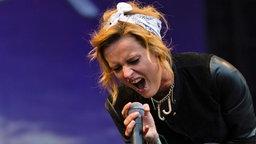 Sängerin Jennifer Weist von der Band Jennifer Rostock singt mit beim Deichbrand Festival 2013 mit viel Pathos ins Mikro. © NDR Foto: Andreas Kluge