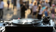 Ein Plattenspieler. Im Hintergrund tanzende Menschen. © NDR Foto: Benjamin Hüllenkremer
