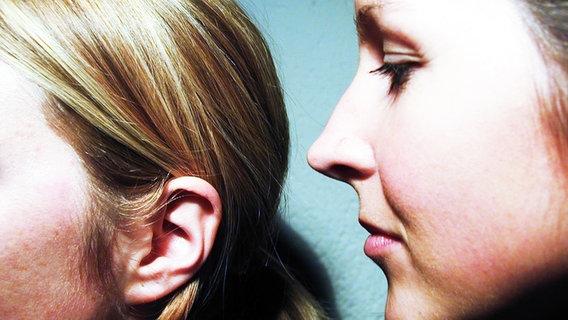 Ein Mädchen flüstert einem anderen etwas ins Ohr. © photocase.de Foto: wagg66