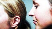 Ein Mädchen flüstert einem anderen etwas ins Ohr. © Plainpicture  / Gallery Stock Fotograf: Anastasia Cazabon