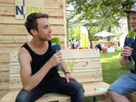Sänger Clueso mit N-JOY Reporter Dennis Dabelstein auf Holzbänken im Grünen. © NDR